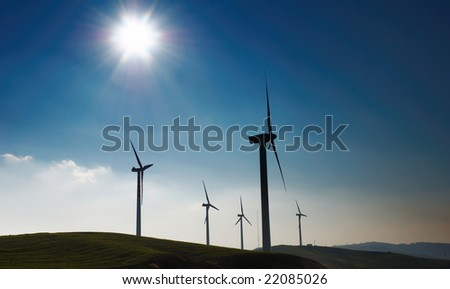 Four wind turbines silhouettes on top of hill
