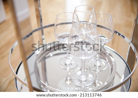four wine glasses on the stainless steel shiny bar tray