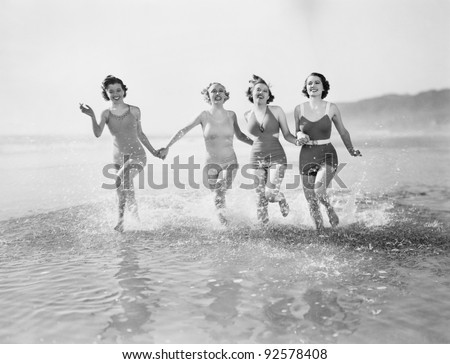 Four women running in water on the beach - stock photo