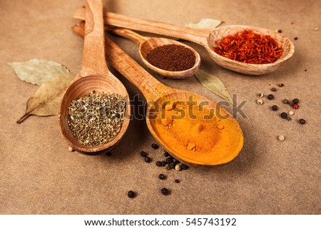 Four wooden spoons with different spices on brown backdrop.
