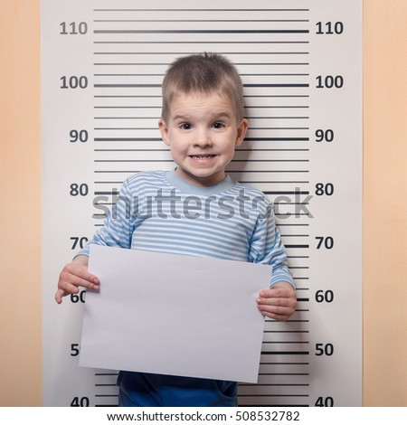 Four year old boy boy holding a white poster while standing against police line-up