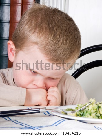 Four year old boy disliking the food on his plate - stock photo