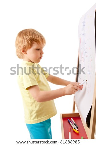 Four-year old boy drawing picture on easel. Isolated on white