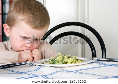 Four year old boy refusing to eat his dinner - stock photo