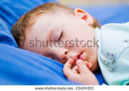 four year old boy sleeping in his bed (shallow DOF) - stock photo