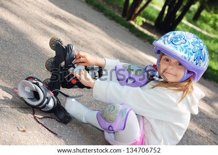 Four year old child putting on her in-line skates. - stock photo