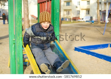 Four-year-old kid plays at a playground in the winter - stock photo