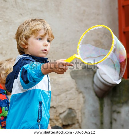 Four years old caucasian child boy blowing soap bubbles outdoor on birthday party - happy carefree childhood. Kid having fun. - stock photo