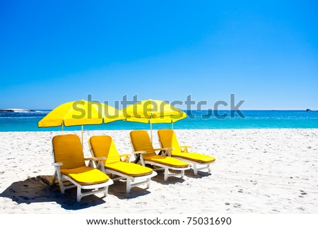 Four yellow beach chairs under two umbrellas on the beach.