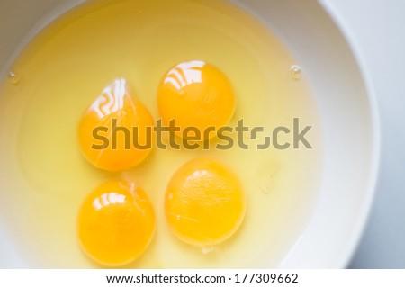 Four yellow egg yolks in a white bowl. - stock photo