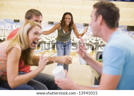 Four young adults laughing and gesturing in a bowling alley - stock photo