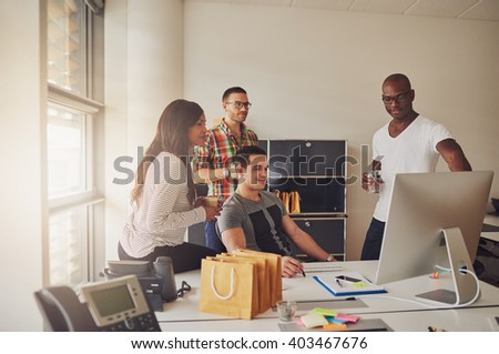Four young adults sitting around desk with computer, telephone, sticky notes and pen and paper next to bright office window - stock photo