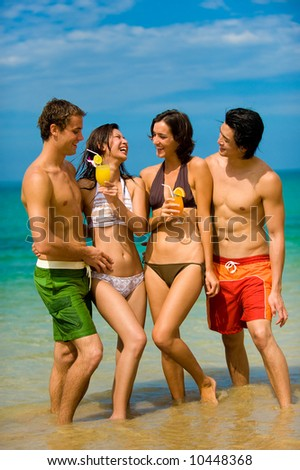 Four young adults standing by ocean with drinks - stock photo