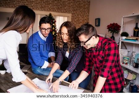Four young architects working on a project, teamwork, building trust