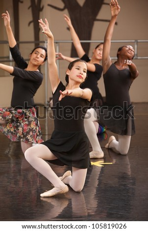 Four young ballet performers kneeling on floor - stock photo