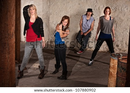 Four young break dancers posing in underground setting - stock photo