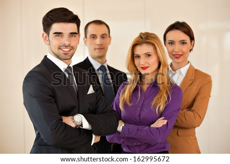 Four young business people, two men and two women, smiling  with their arms crossed - stock photo