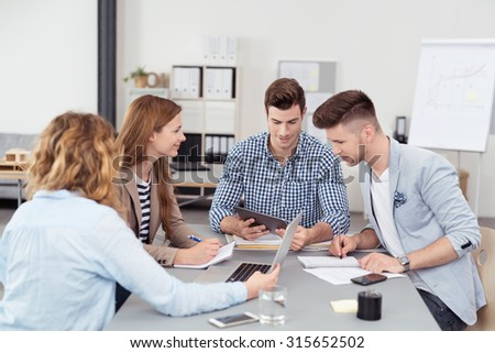 Four Young Businesspeople Having a Business Meeting Inside the Boardroom using Portable Tablet and Laptop Computers