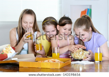 Four young cheerful girls relaxing at home together - stock photo