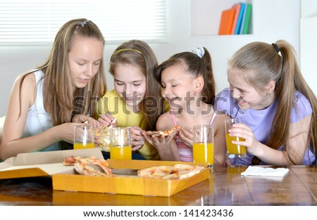 Four young cheerful girls watching TV together - stock photo