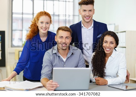 Four Young Cheerful Office Workers at the Table with Laptop Computer, Smiling at the Camera. - stock photo