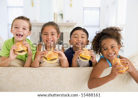 Four young children eating cheeseburgers in living room smiling - stock photo