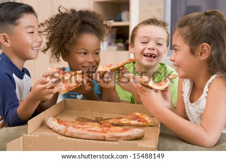 Four young children indoors eating pizza smiling - stock photo