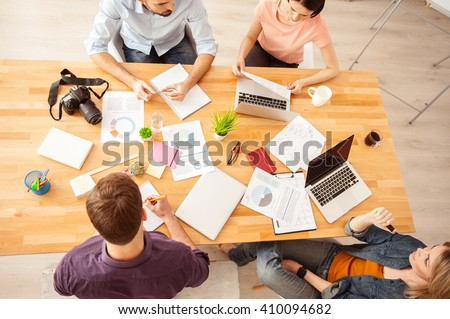 Four young colleagues are talking about work - stock photo