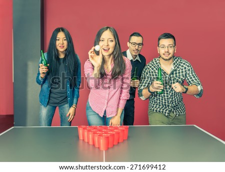Four young college students playing at beer pong in a hostel - Group of multiracial friends drinking beer and having fun -concepts about youth,party and social gathering - stock photo