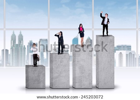 Four young entrepreneurs standing on business chart, symbolizing their achievement - stock photo
