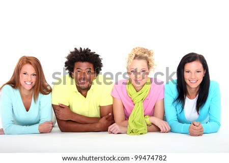Four young friends lying down on the white background - stock photo