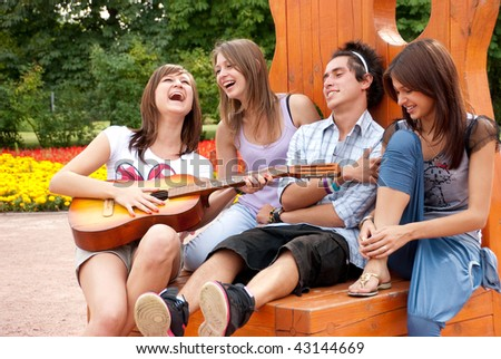 Four young  friends play the guitar and laughing outdoors - stock photo