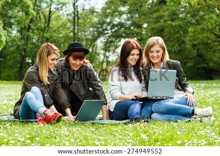 Four young girls sitting in the park and using laptop.Happy girls using laptop - stock photo