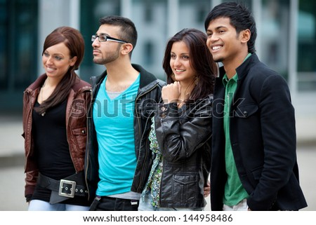 four young happy people walking in the city - stock photo