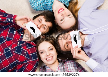 four young men lie together, applied to the face plate with a mustache - stock photo