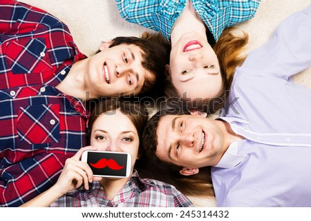 four young men lie together, young attractive woman pressed her lips to the phone - stock photo