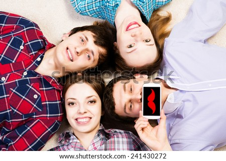 four young people are together, the young man pressed his lips to the phone - stock photo