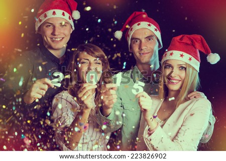 Four young people celebrating New Year, holding card numbers 2, 0, 1 and 5 - stock photo