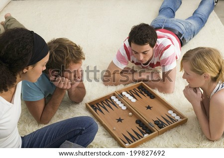 Four young people on floor playing Backgammon - stock photo