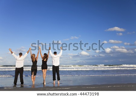 Four young people, two couples, holding hands, arms raised having fun and celebrating on a beach