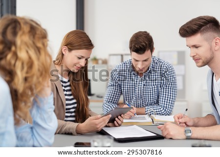 Four Young Professional People In Casual Clothing Having a Business Meeting at the Table Inside the Office - stock photo