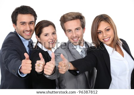 Four young professionals giving the thumbs up - stock photo