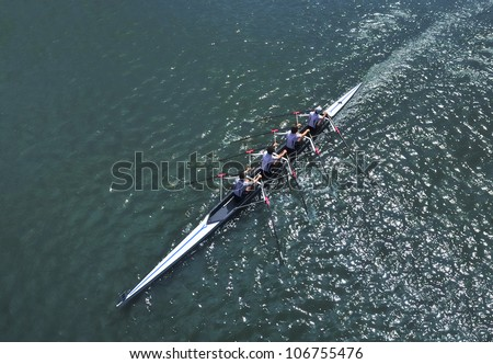 Four young sportsmen rowing  on a sunny day - stock photo