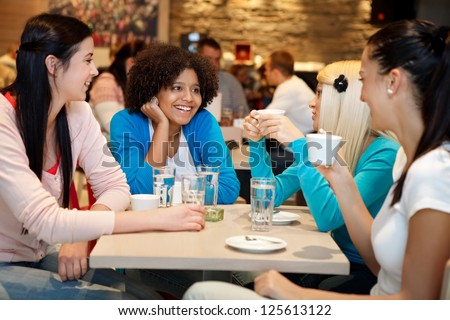 Four young woman college chatting in a coffee shop - stock photo