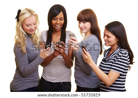 Four young women reading text messages on their cell phones - stock photo