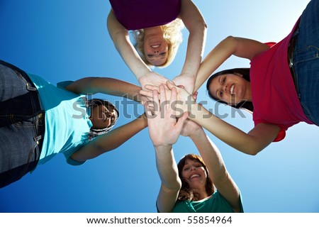 Four young women stacking their hands on top of each other - stock photo