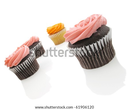 Four yummy cup cakes with colorful icing on white - stock photo