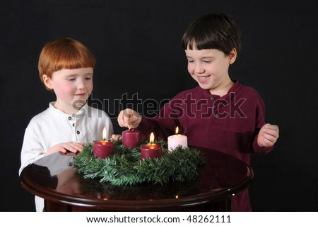 Fourth Week of Advent: Two brothers light an Advent wreath to prepare for Christmas - stock photo