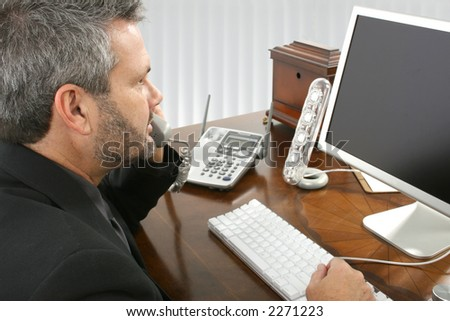 Fourty something business man in suit sitting at desk looking at monitor talking on telephone. - stock photo