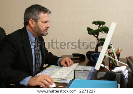 Fourty something year old business man looking concerned at computer screen. - stock photo